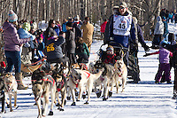 John Dixon and team run past spectators on the bike/ski trail during the Anchorage ceremonial start during the 2014 Iditarod race.<br /> Photo by Britt Coon/IditarodPhotos.com