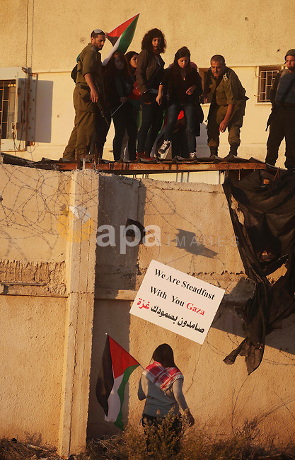 Palestinian feminine activists break inside a military camp near the West Bank city of Ramallah on Nov. 15, 2012. About 20 Palestinian activists Break in Biet Eil militarily camp rising Flags and banners supporting Gaza Strip, 7 of them were arrested. Photo by Issam Rimawi