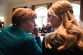 German Chancellor Angela Merkel (L) wispers with Ivanka Trump during a roundtable discussion on vocational training with United States and German business leaders in the Cabinet Room of the White House in Washington, DC on March 17, 2017.       <br /> Credit: Photo by Pat Benic / Pool via CNP