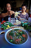 Couple eating pho, Vietnamese tradditional noodle soup at To-chau restaurant, Chinatown, Honolulu, Oahu