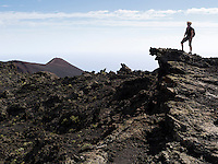 A female hiker stands on a rock in the volcanic landscape between the two volcanos San Antonio and Teneguia (in the background) on the Canary Island of La Palma.