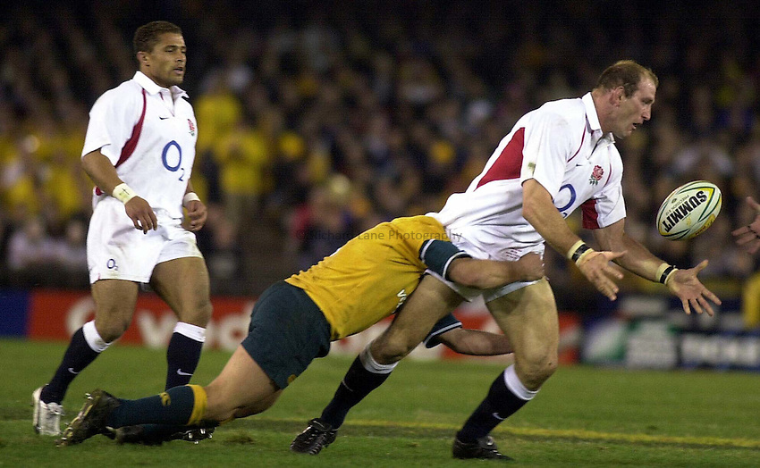 Photo. Steve Holland .Australia v England Rugby Test Match in Melbourne, Australia. 21-06-2003.Lawrence Dallaglio makes the pass under pressure as Robinson looks on