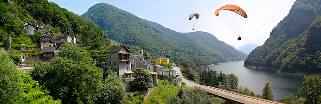 Para gliders over the rustic alpine village of Vogorno with paragliders over lake Vogorno, Val Verzasca, Tocino Switzerland