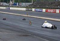 May 29, 2013; Englishtown, NJ, USA: John Force Racing team track specialist Lanny Miglizzi inspects the surface of Raceway Park prior to the Summer Nationals. Mandatory Credit: Mark J. Rebilas-