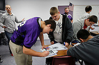 NWA Media/DAVID GOTTSCHALK - 12/18/14 - Levi Bootwala (cq) , left, an eighth grade student at Oakdale Middle School in Rogers, signs a certificate upon the completion of the 16 week program The R.E.A.L. Man  at the school December 18, 2014. The character development program The R.E.A.L. Man program, respect all people, especially women, always do the right thing and live a life that matters,  taught by Ray Keller, a physical education teacher and head football coach, and Jeff Smith,  a history teacher and assistant football coach, was offered to eighth grade boys finished after 16 weeks with a recognition ceremony.