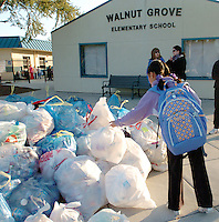 Students and parents from Walnut Grove Elementary School gather and recycle cans and plastic bottles to raise money for their classrooms at the School in Pleasanton, California Friday, Jan. 30, 2009. The school earns thousands of dollars each year through the program while keeping tons of garbage out of landfills. The program is part of the 'Go Green' initiative founded by Pleasanton resident Jill Buck.  (Photo by Alan Greth)