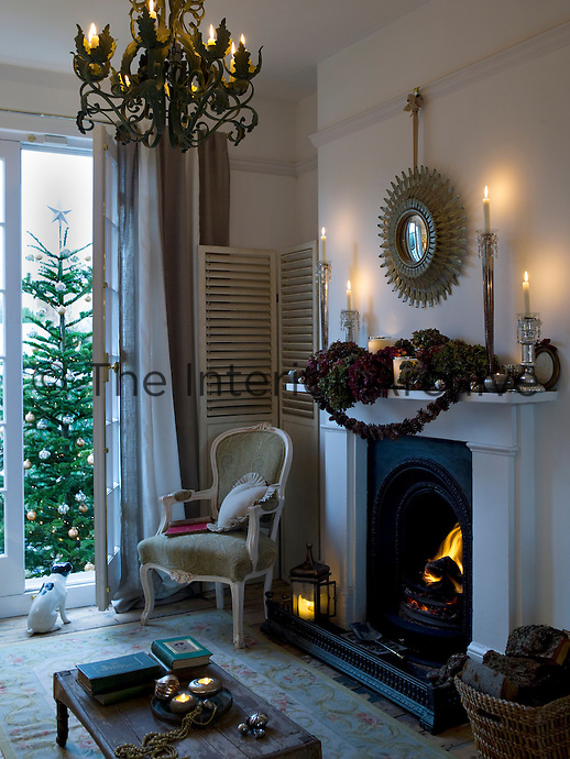 The mantelpiece has been decorated with dried hydgrangeas, candles and a pine cone garland