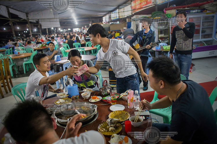 A group of Chinese tourists drink and dine at a restaurant in Mong La. Different kinds of live animals ranging from snakes and pangolins to turtles and others are kept in cages in front of the wildlife restaurants. <br /> The town of Mong La on the Burma - China border in western Burma (Myanmar) is technically in Burma but relies on most infrastructure - electricity, telecommunications - on neighbouring China. The main currency used here is the Chinese yuan. The town is in the middle of the so-called &quot;Golden Triangle&quot; and specialises in gambling and the sale of poached and endangered species. Tiger skins, rhino horns, pangolins and other creatures are freely traded here and many are available to eat. Prostitution is rife and just outside the town a bear farm keeps between 500 and 600 bears which are kept in captivity for their bile which is harvested for medicinal use.
