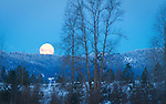 Idaho, North, Silver Valley, Cataldo. A full moon setting behind a ridge in the Coeur d'Alene Mountians before sunrise in winter.