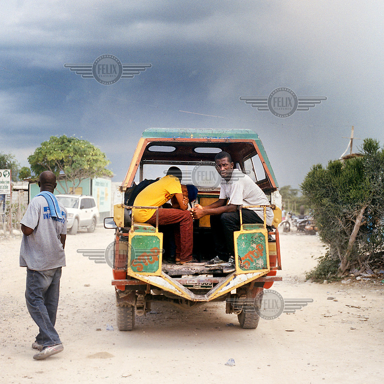 A truck picks up passengers in the new 'Canaan' settlement in Port-au-Prince.<br /> <br /> On 12 January 2010, Port-Au-Prince suffered a 7.0-magnitude earthquake that destroyed much of the city, killing 300,000 people and leaving over a million homeless. Apartment buildings, places of business, governmental buildings, all came crashing down. Wrecked buildings still stand in the city centre where government buildings are being rebuilt. With high unemployment rates prior to the disaster, those who had jobs were now left with no work or with their business premises a heap of broken concrete. <br /> <br /> Five years after the earthquake, thousands of Haitians who were living in the harsh conditions of tent cities were relocated to pre-fabricated one-room wooden houses on the outskirts of the city, while many thousands more, who heard of free land, seized the opportunity to rebuild their homes by hand, with no water, electricity or public services, in a new settlement called Canaan. 'You fall down but you try to get up,' said Julnet Beaucicot, 36, a father of five and a construction worker, who lives in Camp Corail, a community built withNGO funds. Yet, still some 350,000 residents are living in tent camps.
