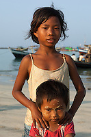 A young girl from the fishing village of Jade Taw on the Bay of Bengal in Myanmar poses for a photograph on the beach with her small sister.