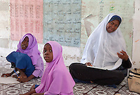 Jambiani, Zanzibar, Tanzania.  African Muslim Primary School Teacher and Two Students.  Swahili is the mother-tongue on Zanzibar, but students also learn Arabic, to be able to read the Koran.