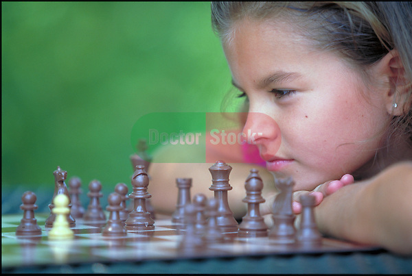 young girl contemplates chess move