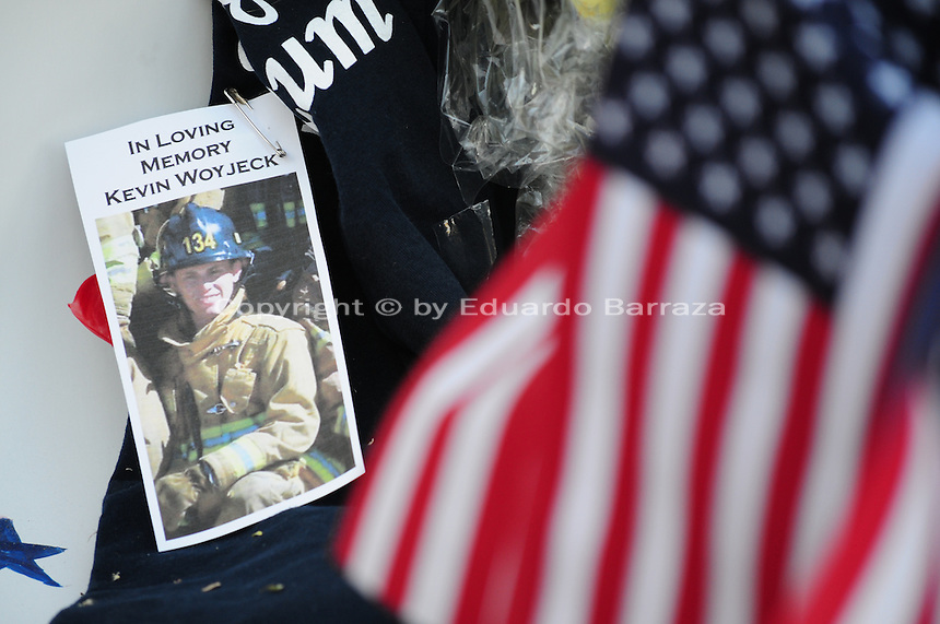 Phoenix, Arizona. July 3, 2013. A small makeshift memorial for the 19 Arizona firefighters who died on June 30 battling the Yarnell Hill wildfire was built outside the Forensic Science Center in Phoenix, where autopsies are being conducted. The photograph of 21-year old Kevin Woyjeck is seen near an American flag to pay tribute to him and the other 18 firefighters who died on Sunday, June 30, 2013 in Arizona. His father, Joe Woyjeck, was a captain with Los Angeles County Fire. Photo by Eduardo Barraza © 2012