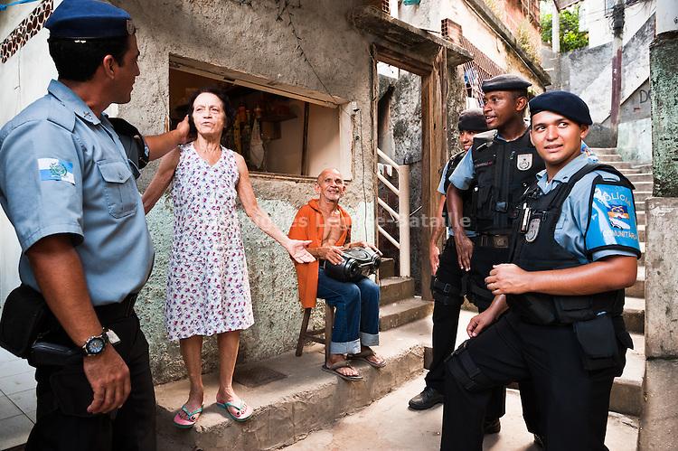 Une patrouille de policiers de l'UPP de Babilonia / Chapeu Mangueira salue Dona Nazinha, une des plus anciennes habitantes de la communauté.