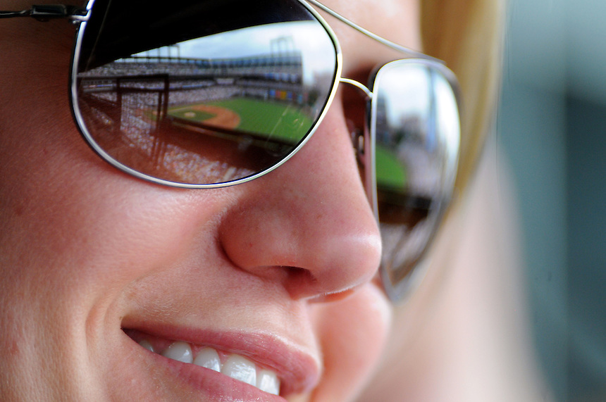 30 JUNE 2011: A female Colorado Rockies fan smiles as she takes in the game in this general view of the stadium is reflected in her ray ban sunglasses   during a regular season interleage game between the Chicago White Sox and the Colorado Rockies at Coors Field in Denver, Colorado. The Rockies beat the White Sox 3-2 in 13 innings.   *****For Editorial Use Only*****
