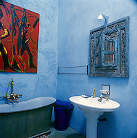 A traditional style blue painted bathroom with a Eastern style mirror above a pedestal washbasin. A freestanding green bath is placed against one wall.