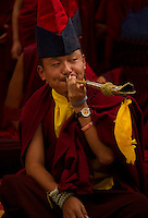 Buddhist Monk playing a musical pipe for a Losar ceremony, Sikkim, India