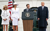 President Emmanuel Macron of France, right center, makes remarks as United States President Donald J. Trump, right,  first lady Melania Trump, left center, and his wife, Brigitte Macron, left, listen at an arrival ceremony for President Macron, on the South Lawn of the White House in Washington, DC on Tuesday, April 24, 2018.<br /> Credit: Ron Sachs / CNP