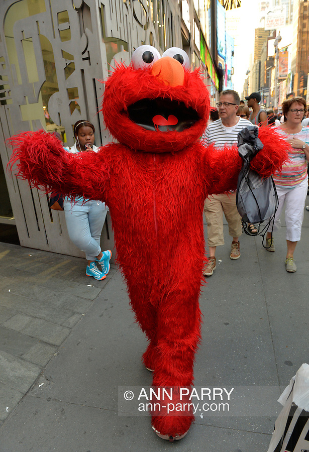 NYC, New York, U.S.  21st May 2013. A person wearing a red Elmo costume, of the Sesame Street character, walks on 7th Avenue during dusk of a pleasant spring day, with a high of 86ºF/32ºC in Manhattan.