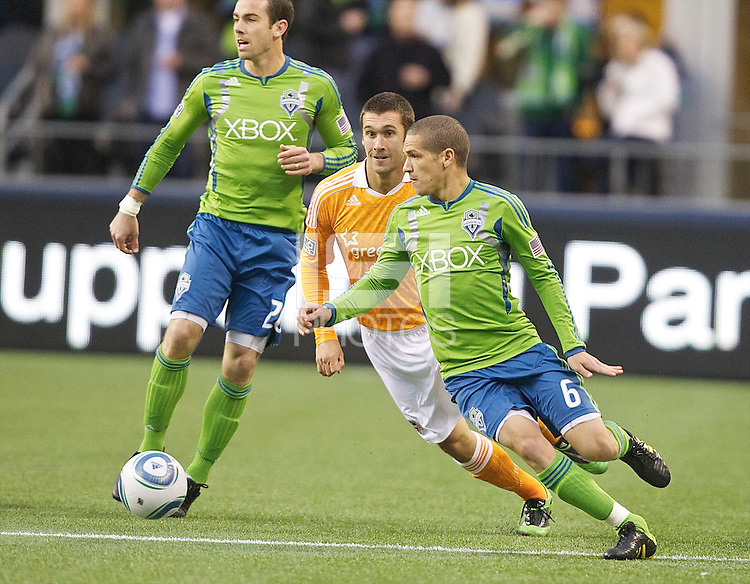 Seattle Sounders FC midfielder Osvaldo Alonso , right, dribbles the ball in front of Houston Dynamo forward Will Bruin during play between at Qwest Field in Seattle Friday March 25, 2011. The match ended in a 1-1 draw.