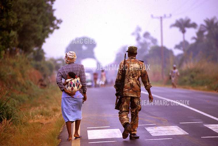 FREETOWN, SIERRA LEONE, DECEMBER 16, 1998 : Polio vaccination campaign during Sierra Leone bloody civil war. A mother takes her child to a  vaccination center while  a government soldier guard the road that leads out of town, toward the frontline and the rebel army of the RUF.(Photo by Jean-Marc Giboux)