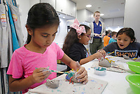 NWA Democrat-Gazette/DAVID GOTTSCHALK Serenity Kanono (left), a second grade student at Walter Turnbow Elementary School, puts the finishing touches Wednesday, October 3, 2018, on her clay creature project inside the Community Creative Center's Wheel Mobile Traveling Art Studio at the school in Springdale. The Wheel Mobile will spend two weeks at the school allowing the each second and third grade student an opportunity to participate in the activity inside the recreational vehicle.
