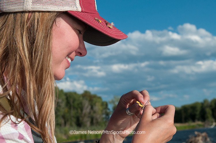 A female angler ties on a fly during a fly fishing trip on the South Fork of the Snake River, Idaho.