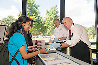 Associate director Reuben Moore, center, and director George Hopper, right, of the Mississippi Agricultural and Forestry Experiment Station, scoop free MSU ice cream for university students, faculty and staff in the MAFES Sales Store on Friday [July 15] to celebrate National Ice Cream Month. (photo by Beth Wynn / © Mississippi State University)