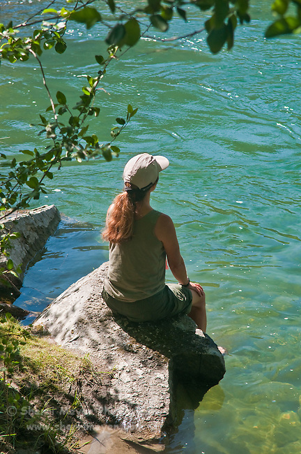 Woman sitting on a rock, enjoying the North Fork of the American River, Weimar, California.