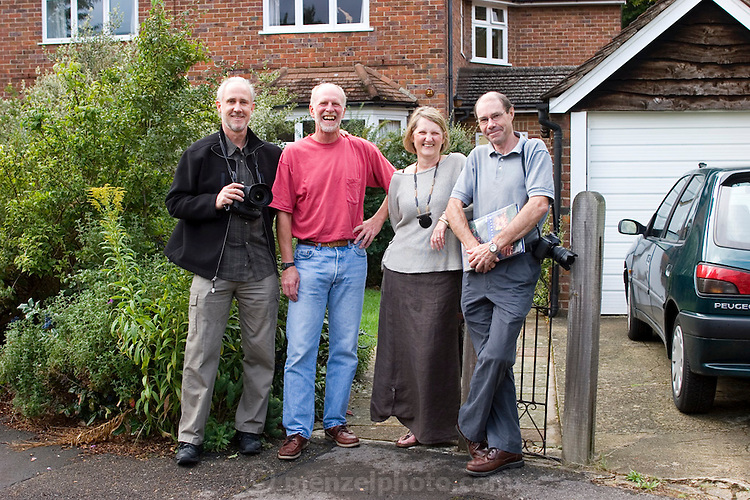 Peter Menzel and David Reed with Richard and Fenella Hodson in front of their house, Godalming, UK. (Material World Family from Great Britain UK) MODEL RELEASED.