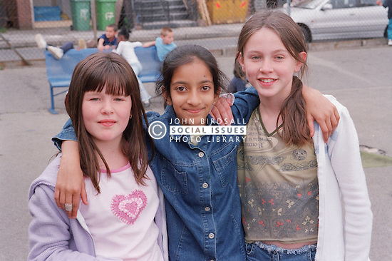 Group of primary school girls standing together in playground smiling,