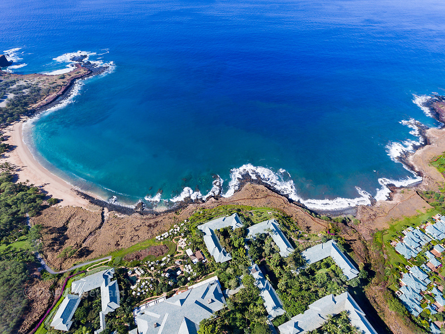 An aerial view of the golden beach and palm tree's at Hulopo'e Beach Park, and the Four Seasons resort at Manele Bay, Lanai Island, Hawaii, USA.