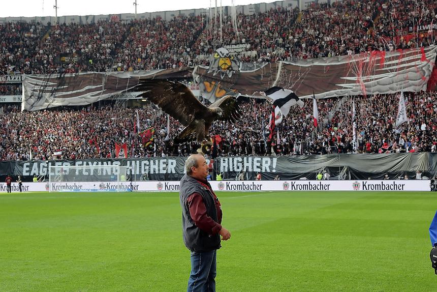 Fans von Eintracht Frankfurt mit ihrer Choreo, davor Maskottchen Attila und Falkner Norbert Lawitschka