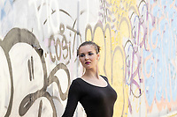 Model wearing black tricot leaning agains a painted wall.