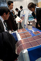 Visitors looking at flexible thin solar cells at the PV Expo 2009, Tokyo International Exhibition Center, Tokyo, 26 February 2009.