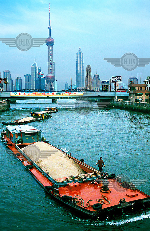 Mark Henley/Panos Pictures..China, Shanghai..Loaded barges in Suzhou Creek, with Pudong financial district skyscrapers and TV Tower behind.