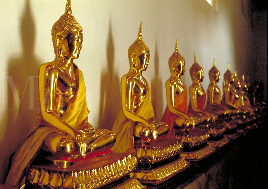 A row of golden Buddhas line the wall of the Wat (Buddhist temple) Mahathat in Bangkok, Thailand. These are statues which are cast from real gold. The rivers and streams of Thailand and Laos were once rich in gold and many of the Buddhas of these cou ntri