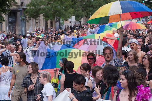 Participants of the Gay Pride March walk with the large rainbow flag of the LGBT movement in Budapest, Hungary on June 18, 2011. ATTILA VOLGYI