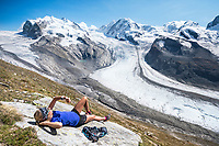 A woman lays on a rock checking her watch while relaxing in the sun with views of the Monte Rosa, Switzerland.