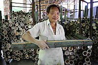 A factory worker holds a piece of bamboo. Bamboo removal in China has grown from 260 million tons in 1990 to 1.2 billion tons in 2005.
