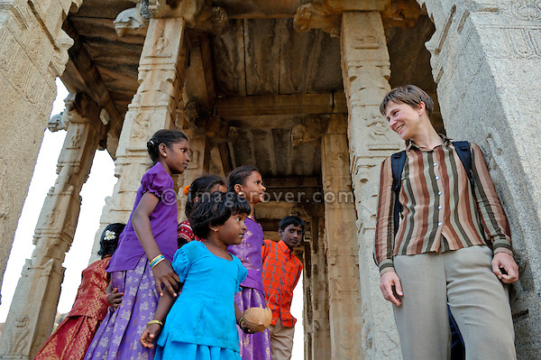 A few indian girls talking to a german mid-aged female tourist at Large Ganesha Temple. Unsesco World Heritage Site of Hampi, India, Karnataka.