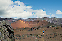Panoramic view of two male hikers in the colorful expansive crater of HALEAKALA NATIONAL PARK on Maui in Hawaii USA