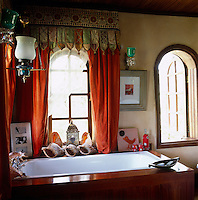 The bathroom windows are draped in orange velvet curtains with Indian pelmets
