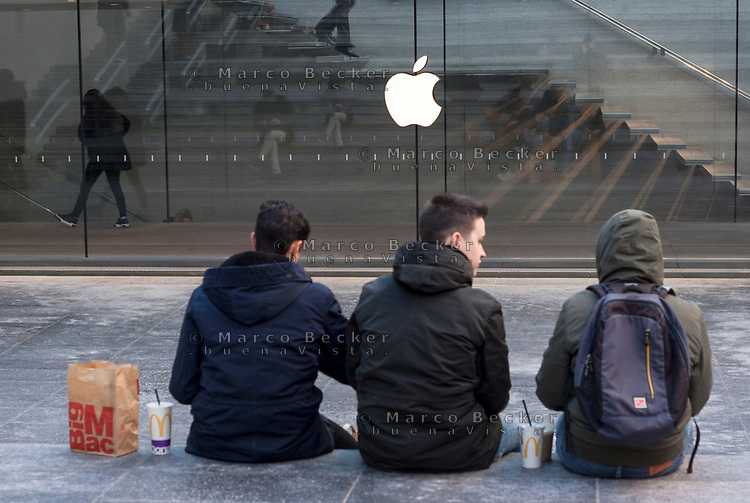 Milano, zona centro. Ragazzi mangiano Mc Donalds davanti l' Apple store. Emblemi di cultura americana --- Milan, downtown. Youngsters eating McDonalds in front of the Apple store. Emblems of American culture