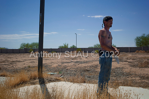 Buckeye, Arizona<br /> July 20, 2012<br /> <br /> 38 yrs old unemployed and homeless, Le Graham scavenges a neighborhood development that stopped 5 years ago when the housing crisis first hit. The property, as many, has weeds grow through the cracks in the cement of what was to be an expansive middle-class neighborhoods. <br /> <br /> <br /> Many of the developments on the outskirts of Phoenix stretched into what use to be farm land stopped in 2008 as the housing market collapsed and money dried up. <br /> <br /> Currently in Phoenix many banks and investors are holding properties and waiting for prices to rise to turn a profit. This depletes the amount of homes on the market and any need for home ownership is harder to find artificially driving prices up in Phoenix by as much as 20% in the past months.