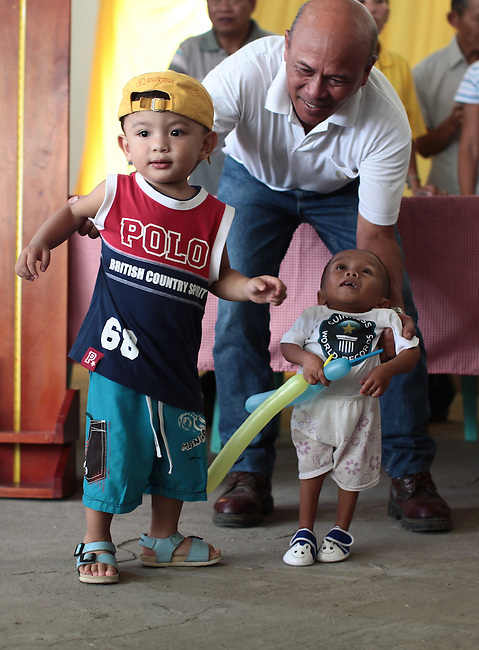Junrey I. Balawing, 18, the world's shortest living man, is pictured next to a two-year-old boy in the town of Sindangan, Mindanao island, Philippines. Balawing, who cannot stand without support, is only 23.5 inches tall.  June 12, 2011. DREW BROWN/MCT