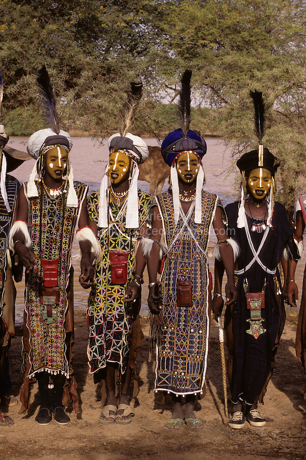 Akadaney, Niger, Africa - Fulani Wodaabe Dancers at Geerewol, often referred to by westerners as the male beauty contest, in which the whiteness of the eyes and the teeth is an important factor in appealing to the female spectators.  Large leather wallets, or red leather amulets, hang from a cord around the neck of the dancers.  Cowrie shells form a fringe on some of the fabric, though this site may be a thousand miles from any sea coast.
