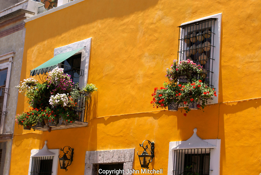 Flower bedecked windows of a restored Spanish colonial house in the city of Puebla, Mexico. The historical center of Puebla is a UNESCO World Heritage Site.