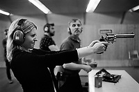 Switzerland. Canton Obwald. Lungern. Brünig Indoor shooting range. A woman is shooting with a cowboy action old-style revolver (P38) during a Jesse James event. 17.05-2017 © 2017 Didier Ruef
